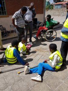 etiopialaisia lapsia istuu maassa tutkimassa tikkuja, pari aikuista seisoo, yksi lapsi on pyörätuolissa