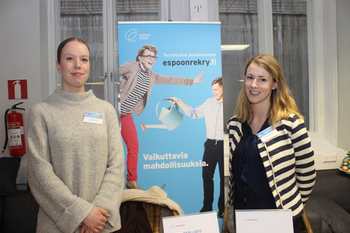 Kaksi naista hymyilee ständillä, takana roll up jossa lukee Espoonrekry