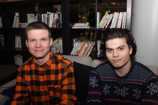 Kaksi nuorta miestä kuvassa, istuvat sohvalla. Vasemmanpuoleisella on päällään punainen ruutupaita, oikenpuoleisella villapaita.
