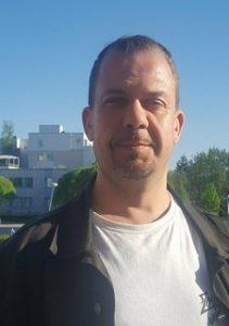 Kuva Caius Treutahardtista, valkoinen paita, musta takki, tummat hiukset, katsoo kameraan