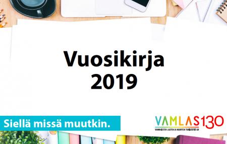 Vuosikirja 2019, slogan ja logo ylhäältä päin kuvatulla työpydällä.
